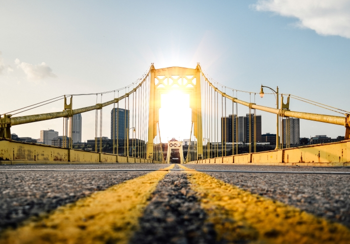 A low angle photo of a yellow bridge utilizing leading line photography